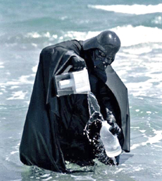Darth Vader standing in the surf, pouring water from a pitcher into a bottle